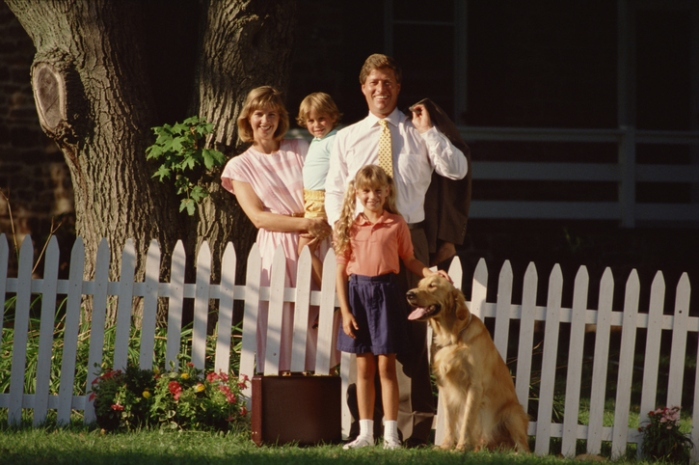 Family by white picket fence